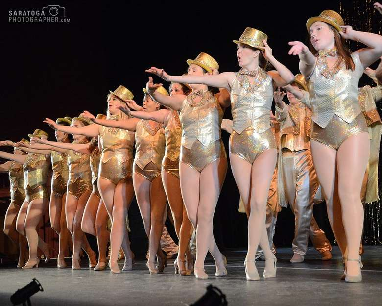 stage full of actors performing in a chorus line, all are wearing gold leotards or pants, vests, and gold top hats