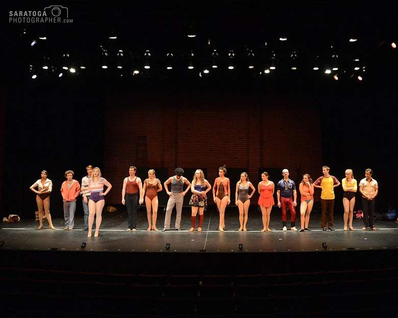 cast of a chorus line in a single horizontal line on stage facing the audience