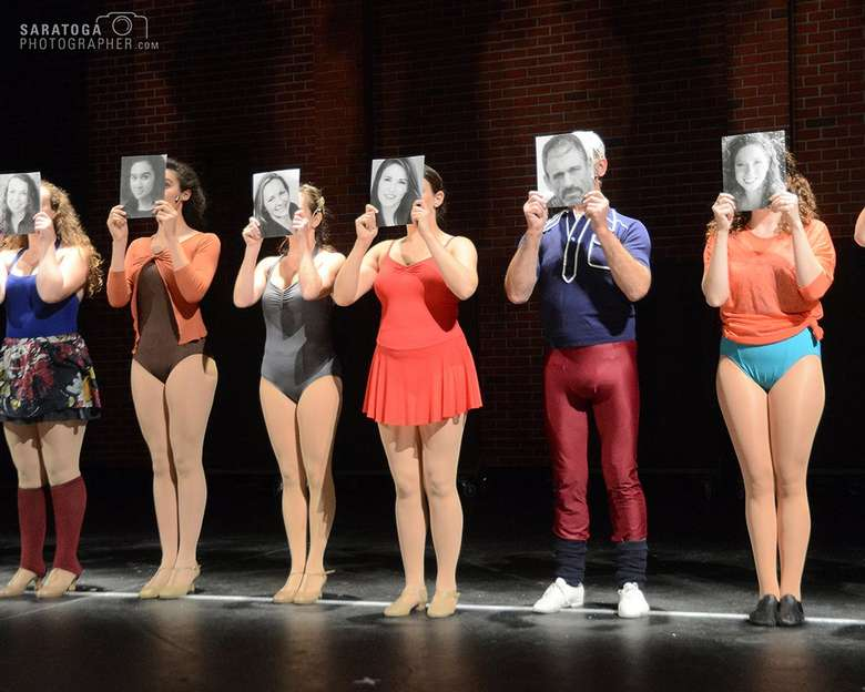 six actors portraying dancers in a chorus line holding headshots in front of their faces