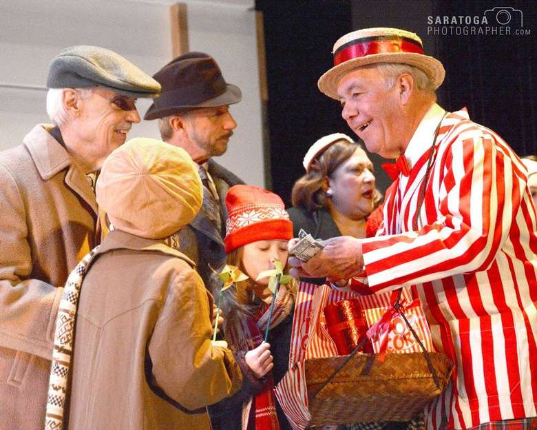 actor wearing a white and red and white striped coat and selling popcorn to other actors