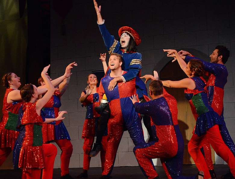 actor playing lord farquad in shrek singing with other actors in red and blue costumes