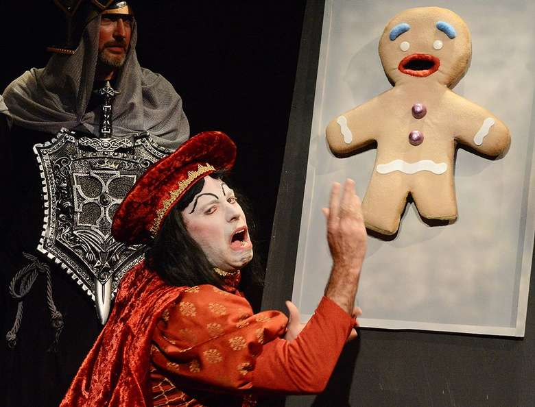 actor portraying lord farquad from shrek interacting with a large gingerbread man made out of foam