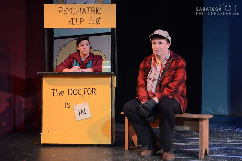actress portraying lucy from the peanuts sitting in a booth that says psychiatric help while an actor portraying charlie brown sits on a bench next to the booth