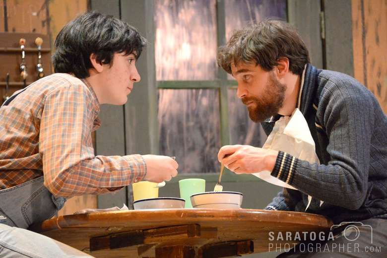 two actors eating out of bowls on stage