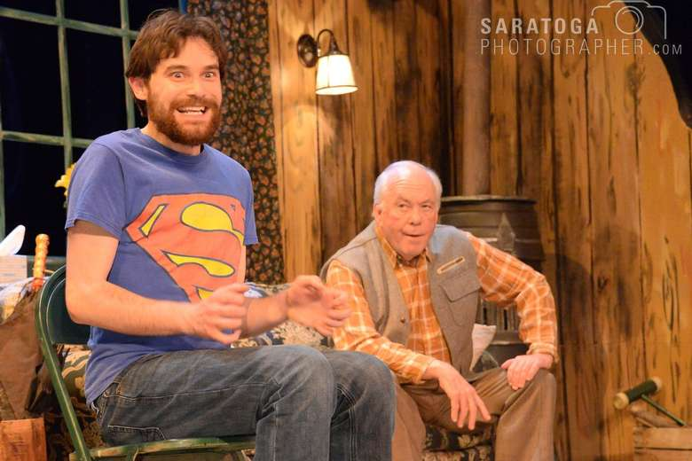 man in a superman t-shirt looking excited while an old man looks on