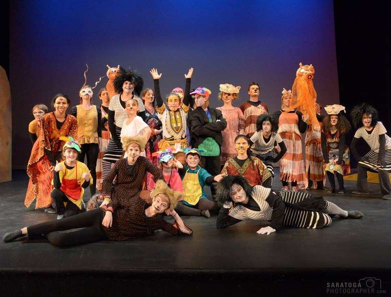 cast of a musical wearing tribal and animal style costumes posing on stage