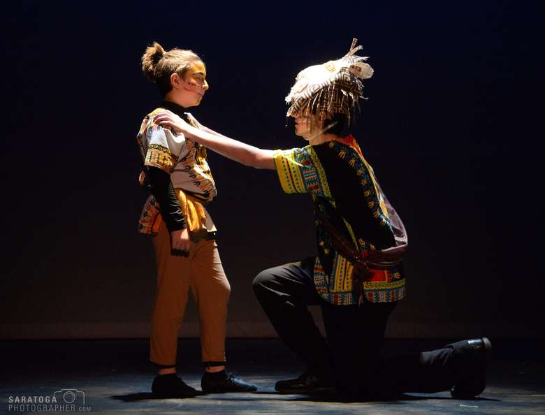 two actors performing on stage in tribal-style costumes
