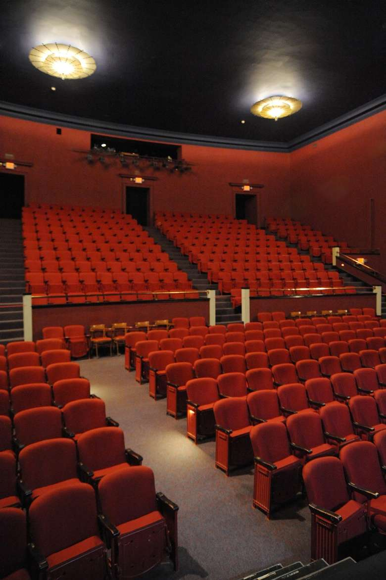 theater auditorium with dozens of red chairs