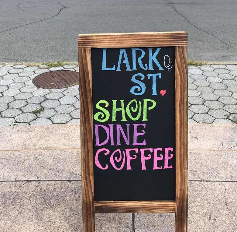 sign that reads lark street shop dine coffee