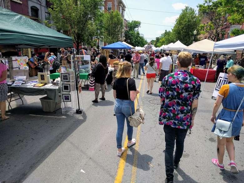 people walking around a street art fair