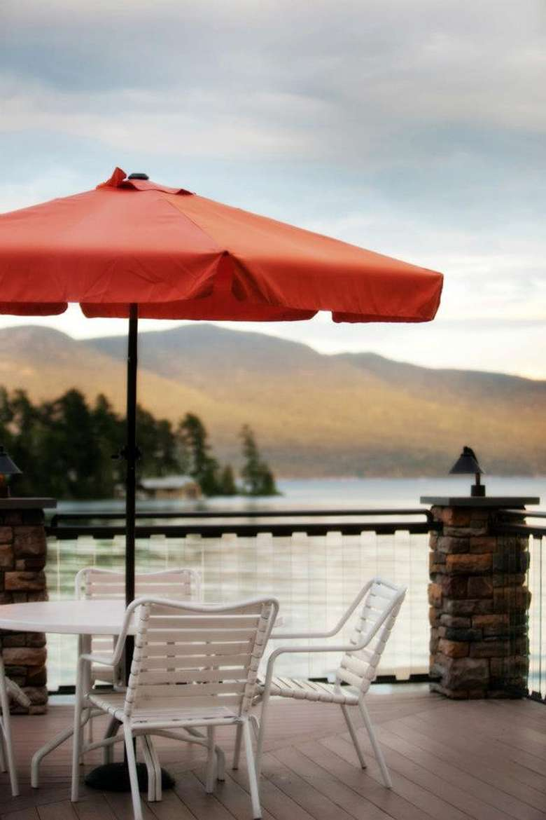 table with chairs and an umbrella on a deck overlooking lake george