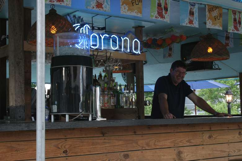 bartender waiting for customers in front of a large lit up corona sign