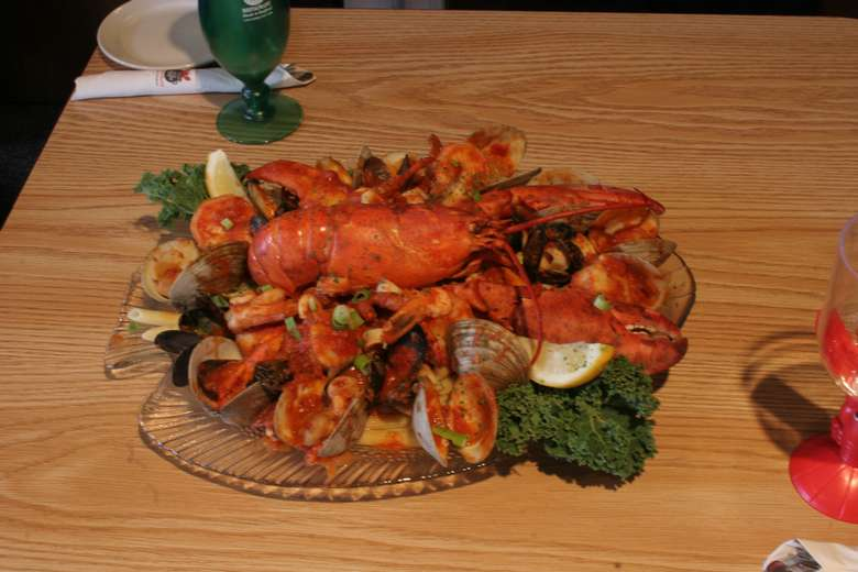 steamed lobster on top of a dish with clams and red sauce