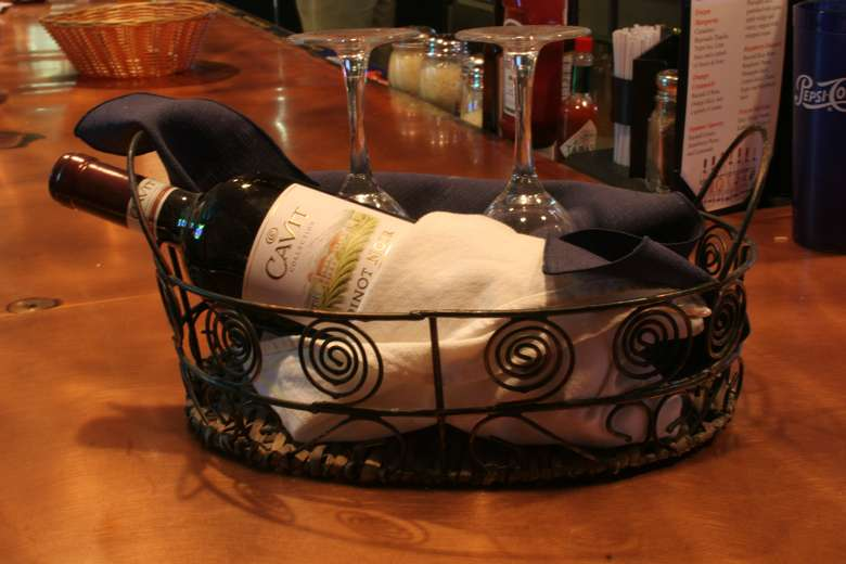 basket containing a wine bottle and two upside-down glasses