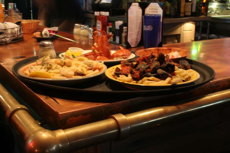 serving tray with three seafood entrees on the edge of a bar