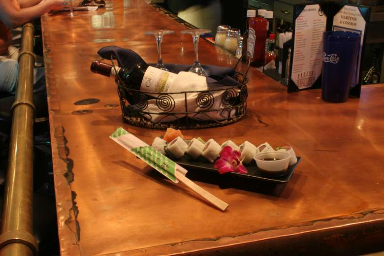 sushi roll with wine bottle and two glasses behind it