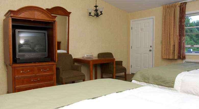 motel room with two beds, seating area, and television cabinet
