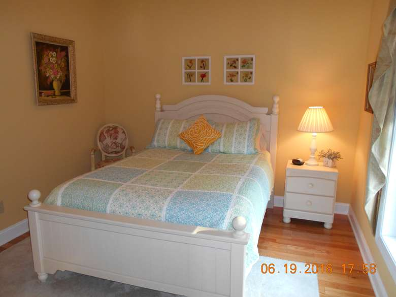 a white bed with a patterned bedspread. There is a small chair to the left and a nightstand to the right of the bed.