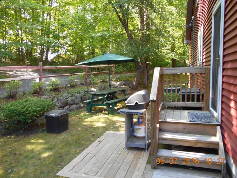a small patio with three steps leading to a side door. There is an outdoor gas grill and a picnic table with an umbrella