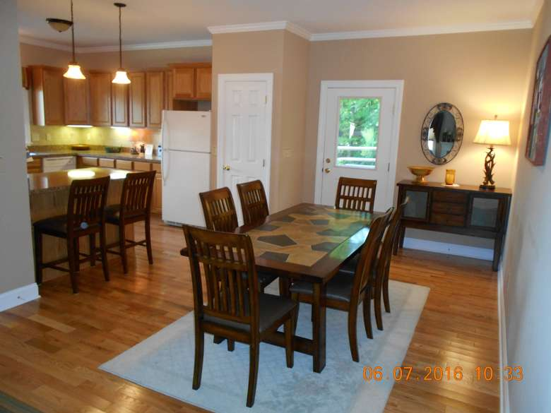 a dining room table seating six, the breakfast bar and open floor plan kitchen are to the left.