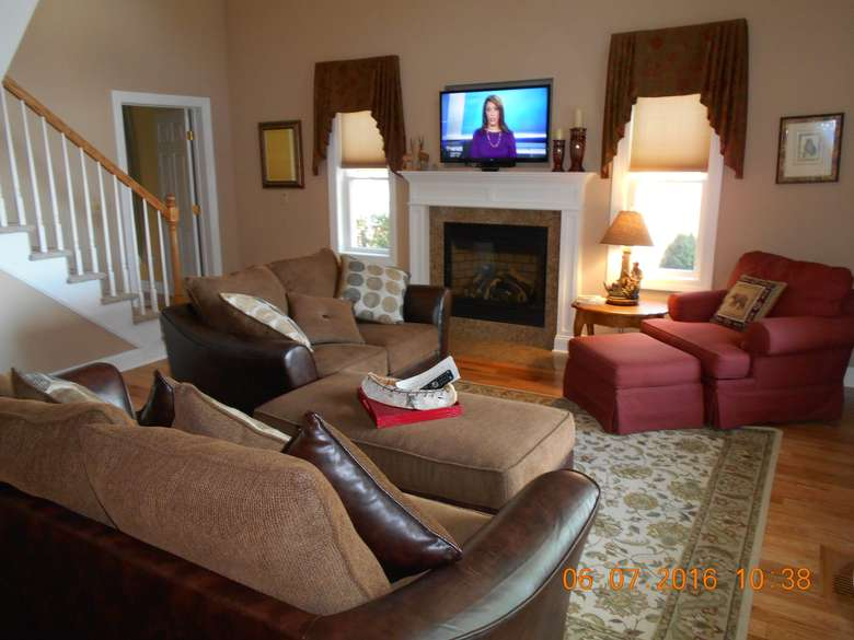 living room containing two couches, chair with ottoman, and a fireplace with a large television above the fireplace