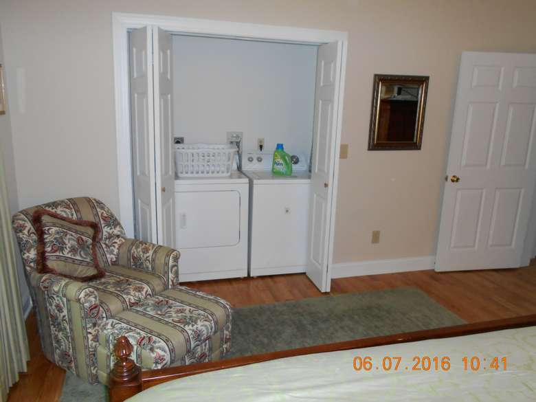 a washer and dryer side by side in an area that can be closed off with accordion doors. There is an upholstered chair and ottoman to the left.