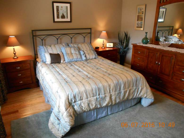a bed with a headboard, nightstands and lamps on either side, and a dresser with a mirror to the right
