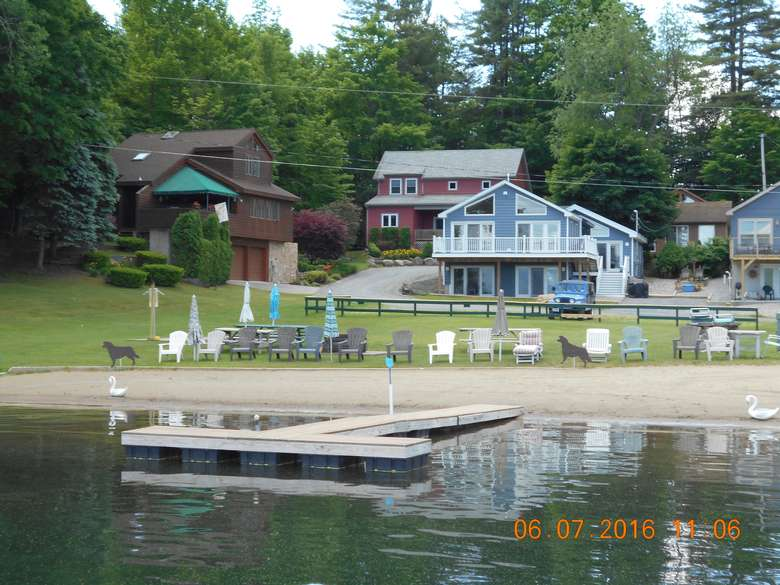 view from the water facing the house, showing docks, a beach, several chairs and beach umbrellas