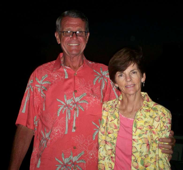 A man and woman in tropical-themed shirts, hugging each other and smiling
