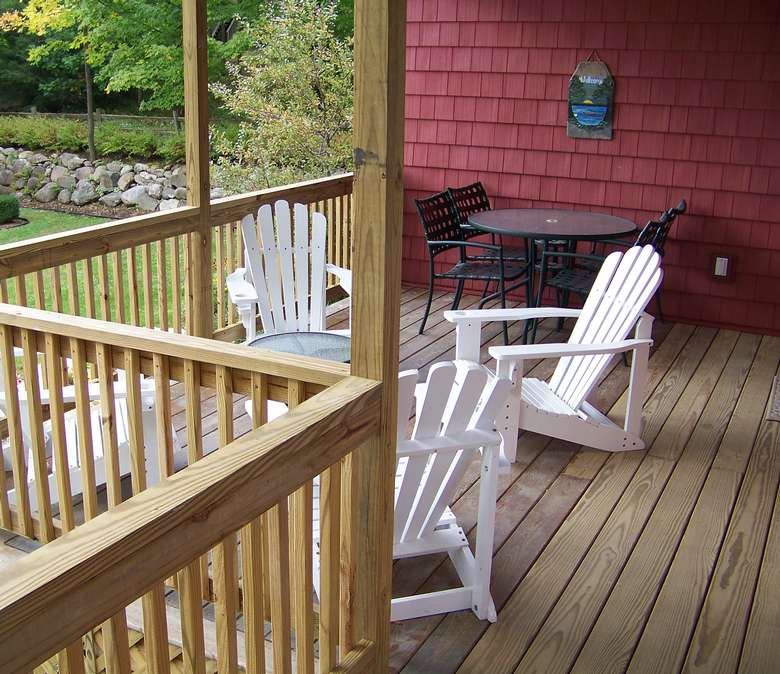 Four white wooden Adirondack chairs surrounding a small circular table. There is a dining table and chairs in the background.