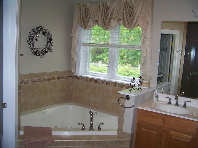 a jetted corner tub with window above and a sink to the right