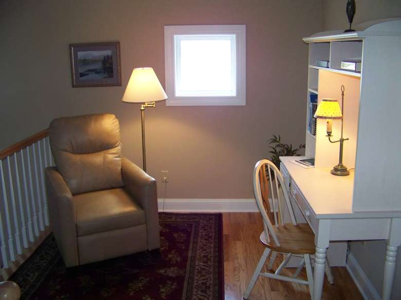 A white wooden desk with a wooden chair. There is another chair to the left, possibly a recliner, with a tall reading lamp next to it.
