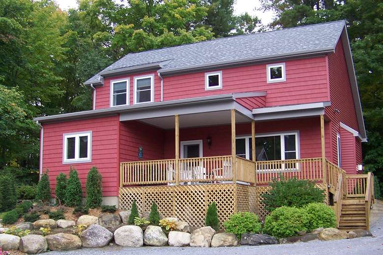 large two-story red house with stairs leading up to a large porch
