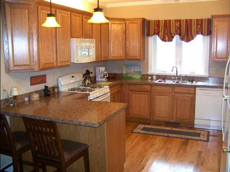 large kitchen with wooden cupboards, breakfast bar, white appliances and a wooden floor