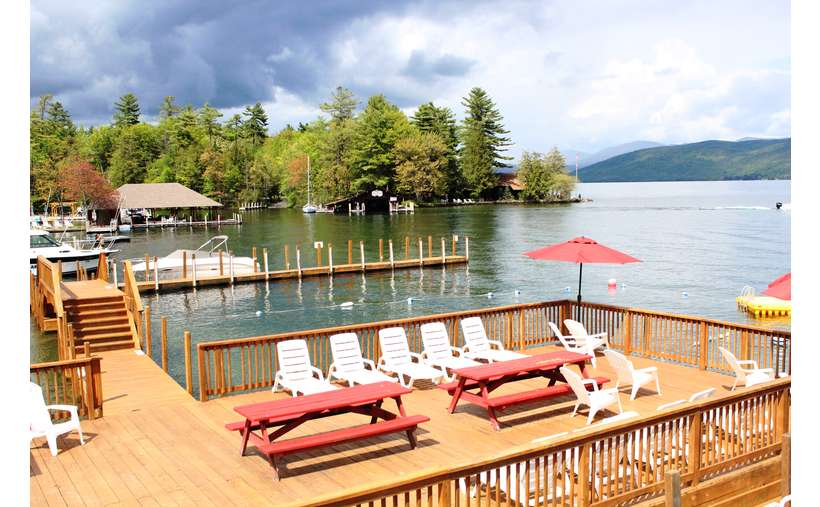 spacious deck on the water with picnic tables and lawn chairs