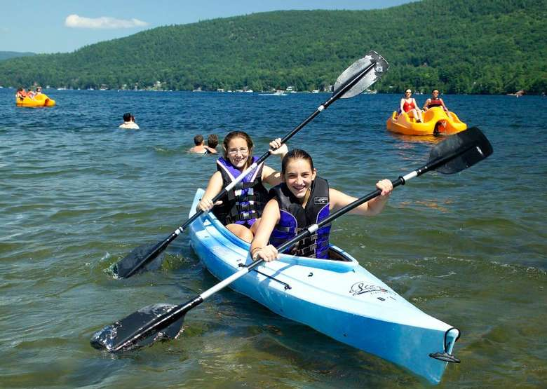 two girls paddling a double kayak