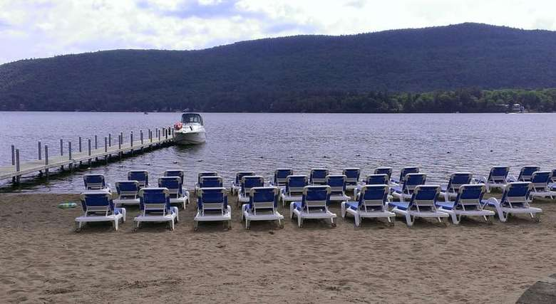 blue lounge chairs set up on the beach in front of lake george
