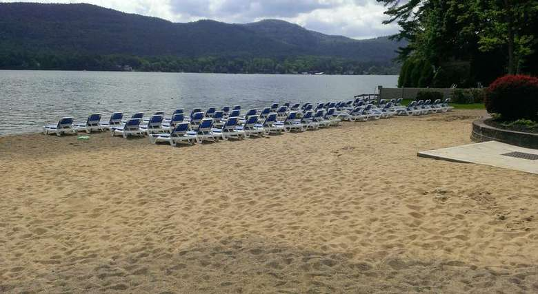 lounge chairs set up on the beach in front of lake george