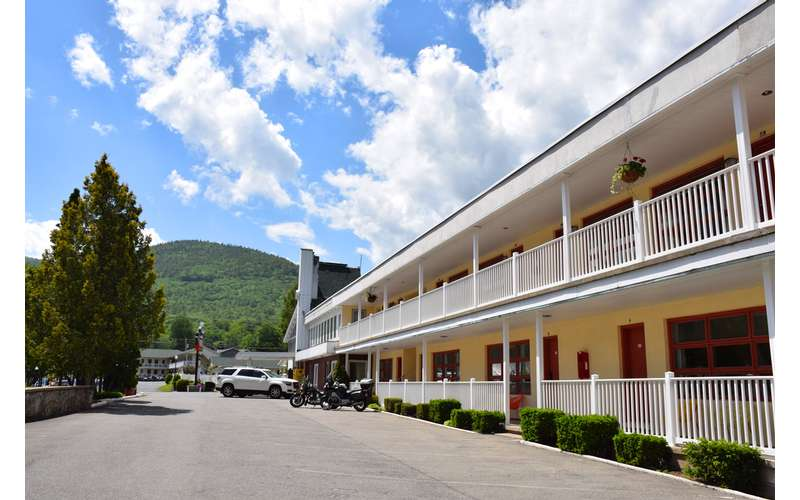 a long motel building with two floors and a covered porch