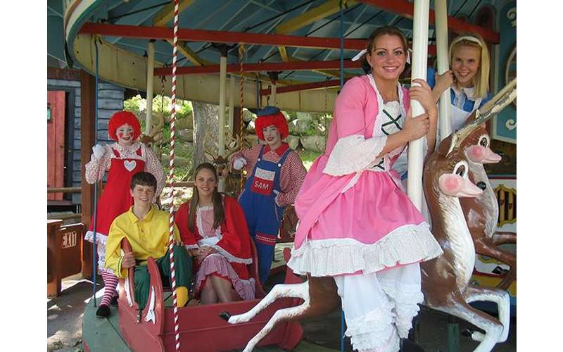 children and cast members on a carousel