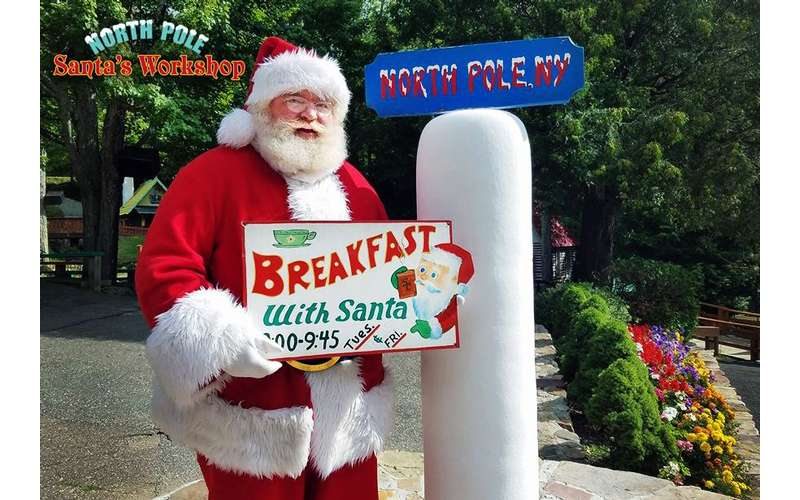 Santa holding a sign that says &quote;Breakfast with Santa