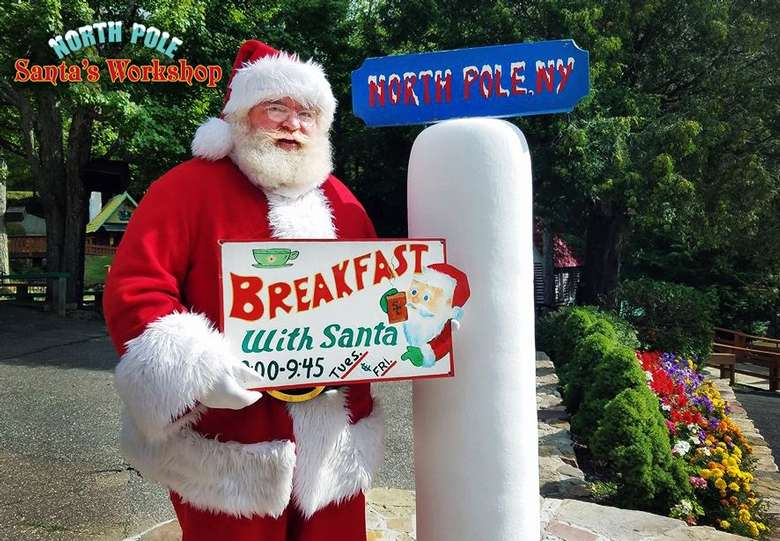 """Santa holding a sign that says """"Breakfast with Santa"""""""