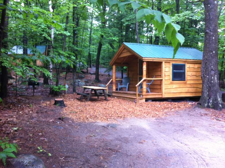 a brown and wooden camping cabin in the woods with a picnic table
