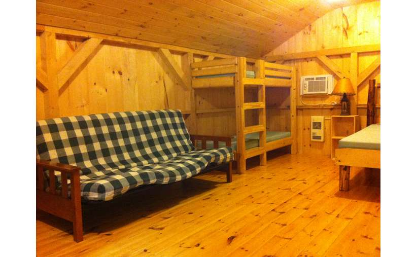 a futon in a camping cabin with a bunk bed nearby