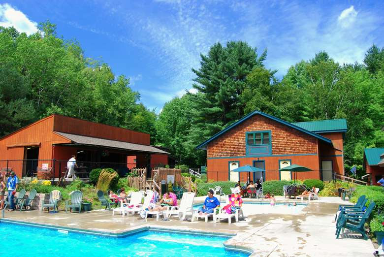 camping cottage buildings in the woods with people near an outdoor pool