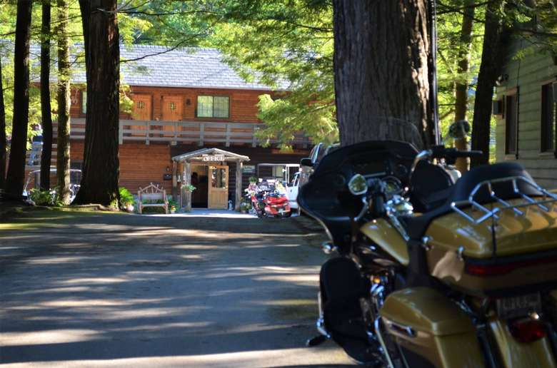 motorcycle in the foreground, cabin in the background