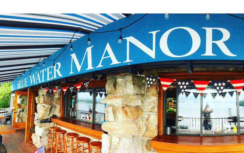 outside of what looks like a restaurant, says Blue Water Manor