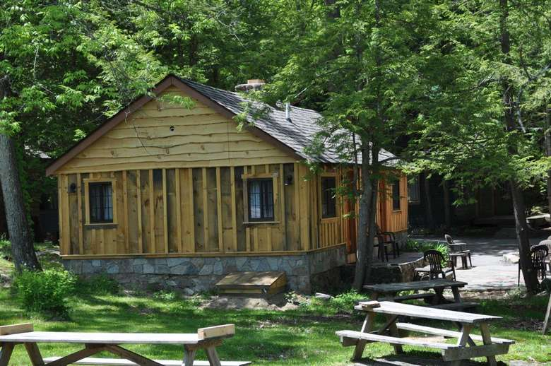 a cabin surrounded by picnic tables and chairs
