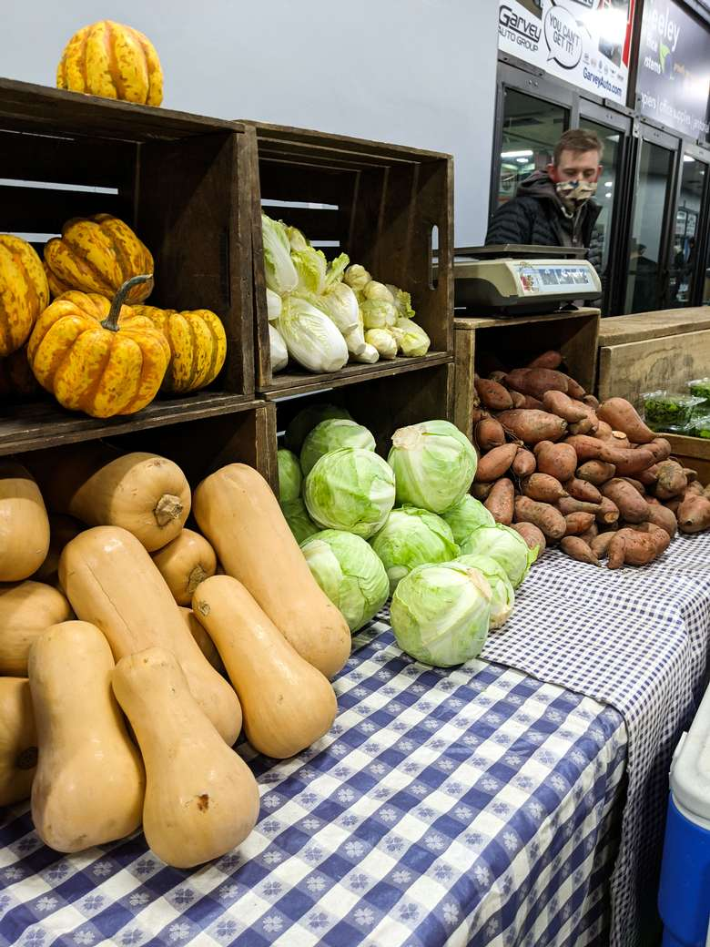 farmers market produce stand with cabbages, squash, and sweet potatoes