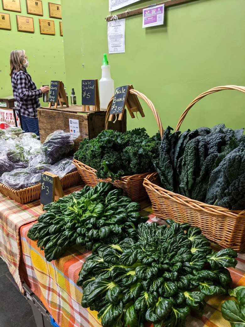 herbs and kale in bushels at a stand